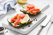 Salmon toast with cream cheese and cucumber on white cutting board, closeup view. Healthy snack, appetizer or breakfast