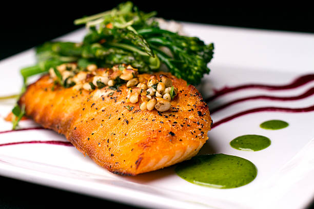 Salmon topped with Pine nuts Scottish Salmon: Pinon-cilantro crusted salmon, baked Himalayan rice,gribiche sauce, vegetables du jour.  aisne stock pictures, royalty-free photos & images