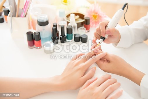 istock salon manicurist using electric nail drill 823559740