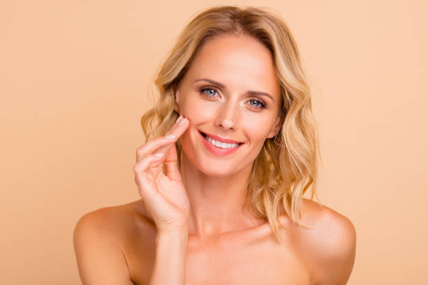 Salon spa therapy treatment concept. Close-up portrait of attractive cheerful wavy-haired lady with flawless smooth pure clean clear skin applying cream on cheek isolated on beige background stock photo