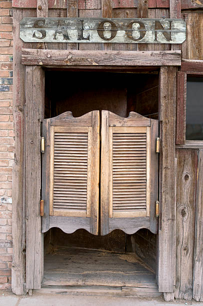 Saloon Doors with Sign Old Western Swinging Saloon Doors with a Saloon Sign Above Doors saloon stock pictures, royalty-free photos & images