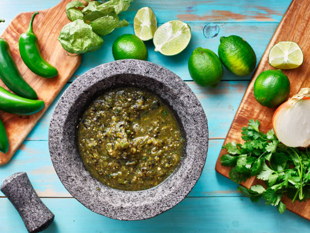 salsa verde in stone molcajete flat lay composition salsa verde in stone molcajete flat lay composition on blue rustic boards salsa sauce stock pictures, royalty-free photos & images