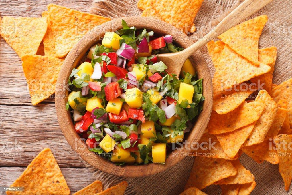 salsa con mango, pimientos, cilantro y cebolla closeup y nachos. vista superior horizontal - Foto de stock de Alimento libre de derechos