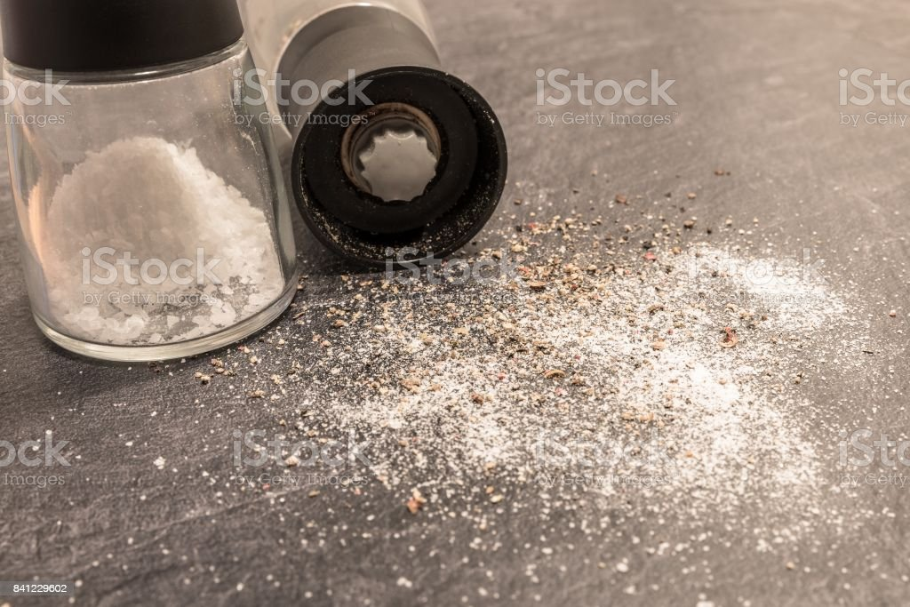 Salt and Pepper mill on grey surface stock photo