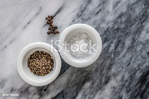 Two small white dishes of sea salt flakes and freshly ground black pepper and scattering of peppercorns. Top down with marble background