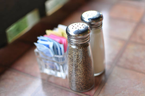 Salt and pepper shakers near box of sweetners stock photo