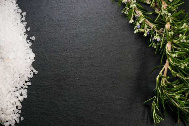 salt and rosemary on a black background stock photo