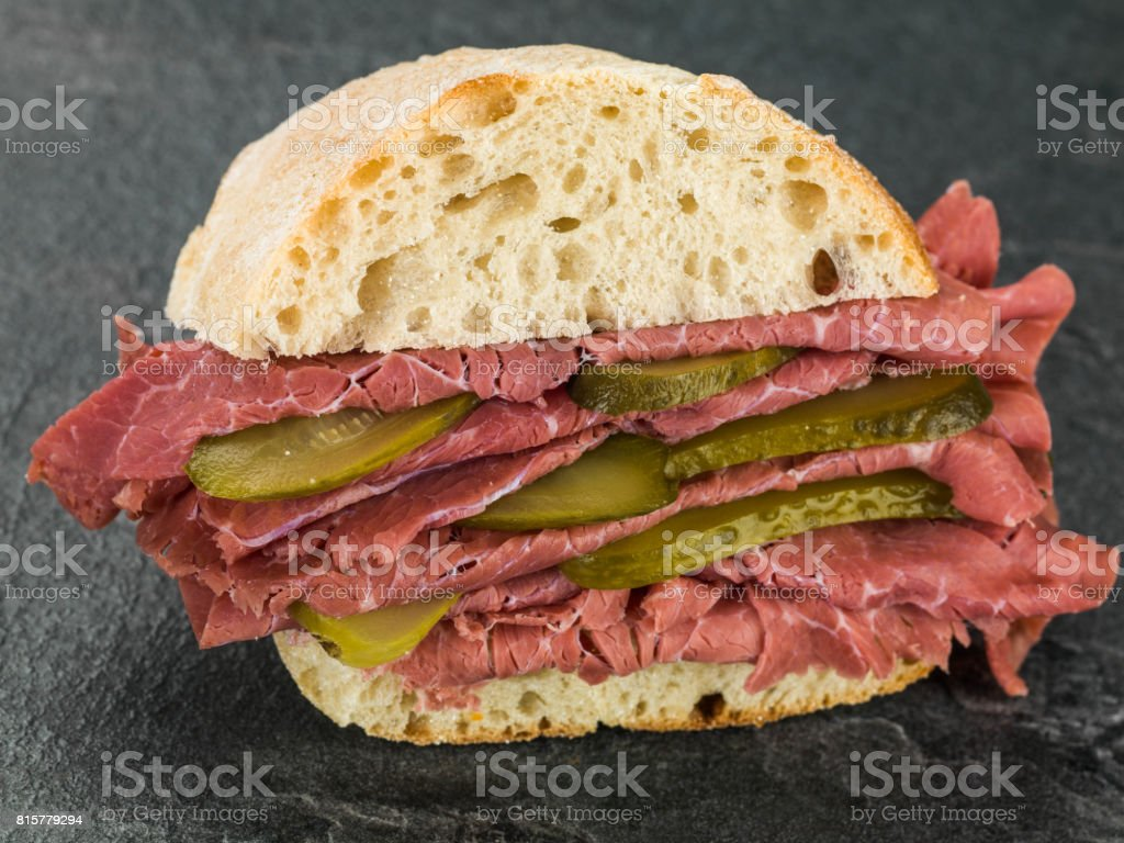Salt Beef or Pastrami With Gherkins in a Ciabatta Bread Roll or Bun stock photo