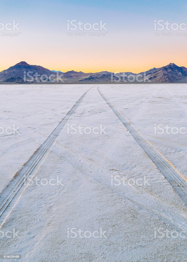 Salt Flats Tracks Tire tracks on the Bonneville Salt Flats with Volcano Peak in distant background left, and Rishel Peak on the right.  Image taken October 2016, Utah, USA Barren Stock Photo