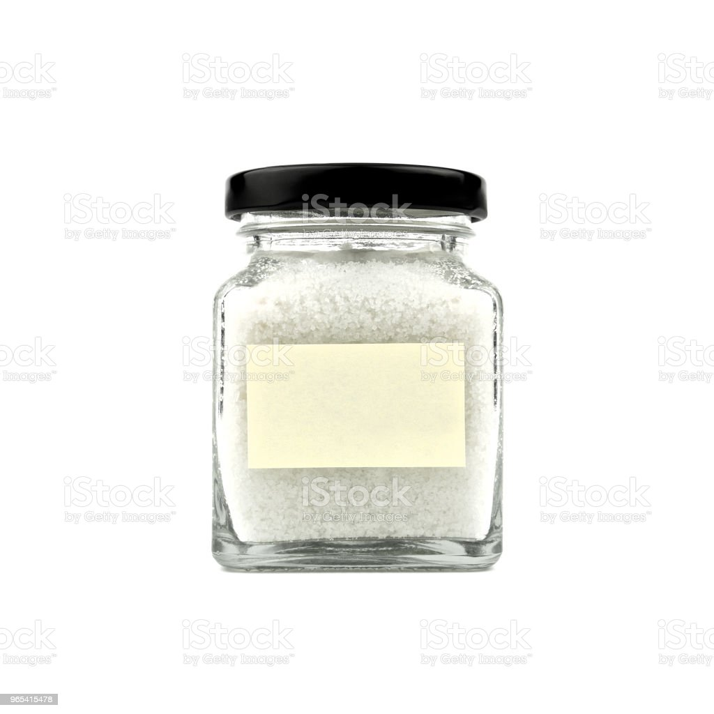 Salt in a glass bottle isolated on white background. Empty yellow stick note paper and black lid. Modern and stylish. Close up. royalty-free stock photo