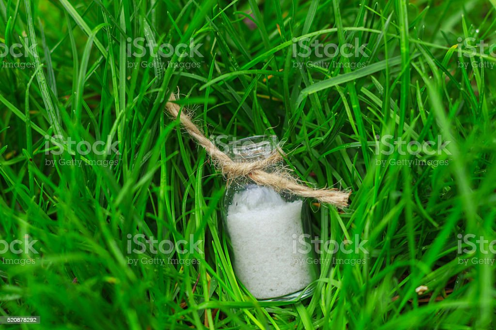 salt in a small jar on the grass stock photo