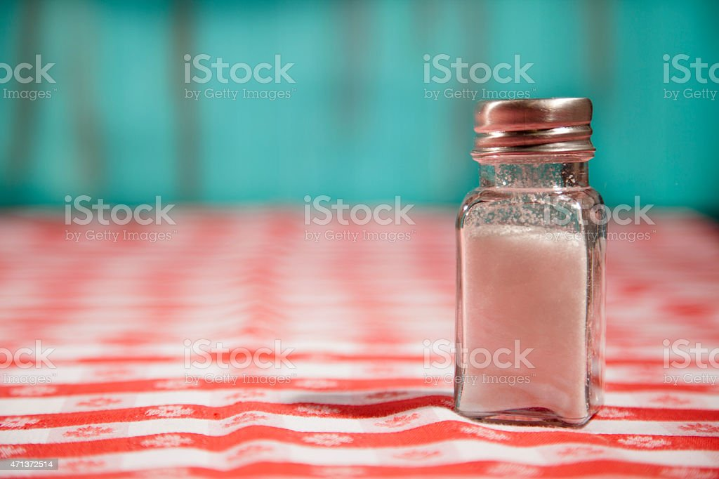 One lone salt shaker filled with salt sits on top of a red checked...