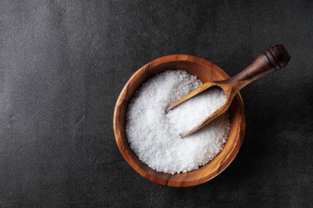 Salt in wooden bowl on black kitchen table top view. Salt in olive wooden bowl on black kitchen table top view. salt stock pictures, royalty-free photos & images