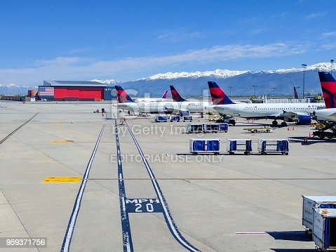 Delta Airlines airplanes lined up at the gates at Salt Lake City airport (SLC) on a beautiful spring day. The mountains in the background are snow capped.