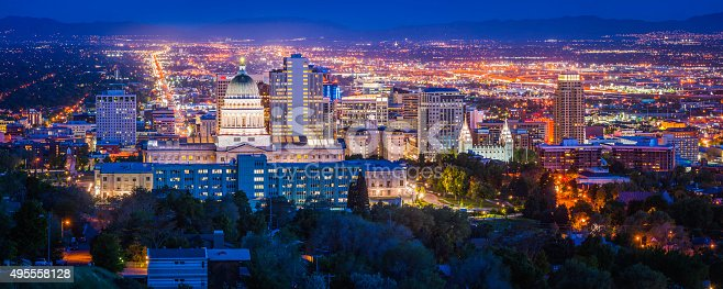 Blue dusk skies over the city lights and landmarks of Salt Lake City, the monument spotlit dome of the State Capitol and the ornamental spires of the Mormon Temple surrounded by the skyscrapers of downtown, Utah, USA. ProPhoto RGB profile for maximum color fidelity and gamut.