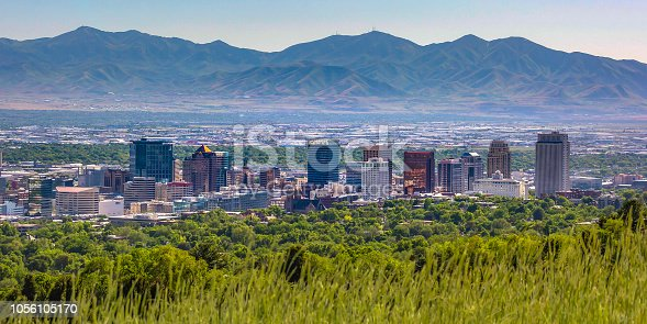 Salt Lake City with buildings and mountain view. Populous Salt Lake City in Utah with buildings and skyscrapers on a sunny day. Trees can be seen in the foreground with mountains in the background.