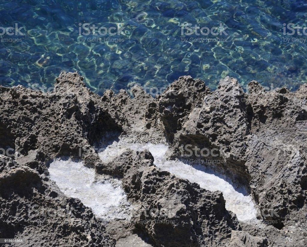 Salt precipitation in eroded black oxidized limestone stock photo