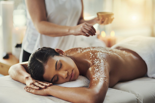 Shot of a young woman getting an exfoliating massage at a spa