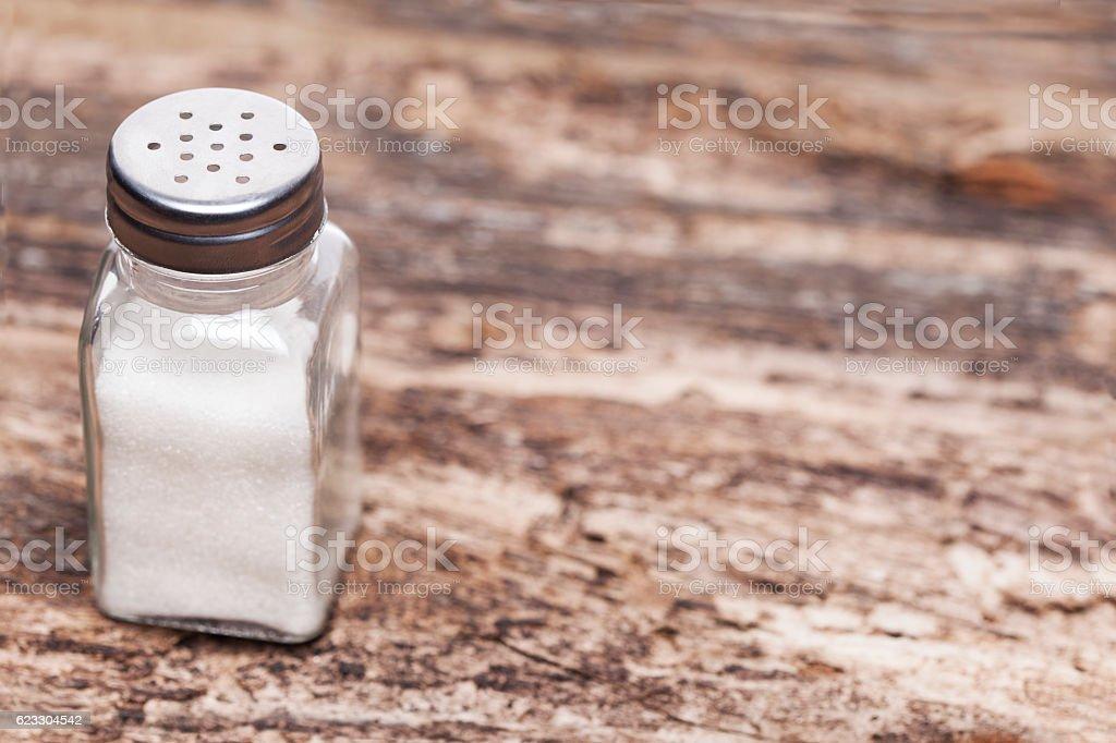 Salt shaker on wooden table stock photo