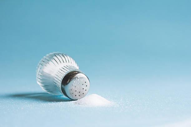 Salt Shaker Spilled salt and saltshaker on blue background salt stock pictures, royalty-free photos & images