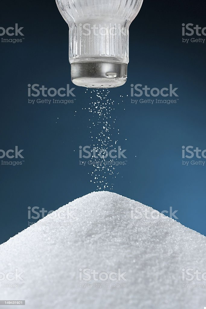 Salt shaker with salt coming out onto big pile stock photo