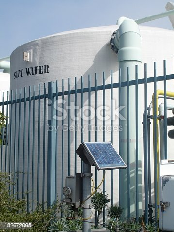 Big metal tanks outdoors behind a fence connecting  tanks for salt desalination process to purify water for Long Beach Aquarium; water purification, water processing, salt,clean, filter,storage tank, electronic controls,nb,day,sun,