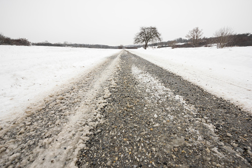 Salt with gravel spread on snowy countryside road
