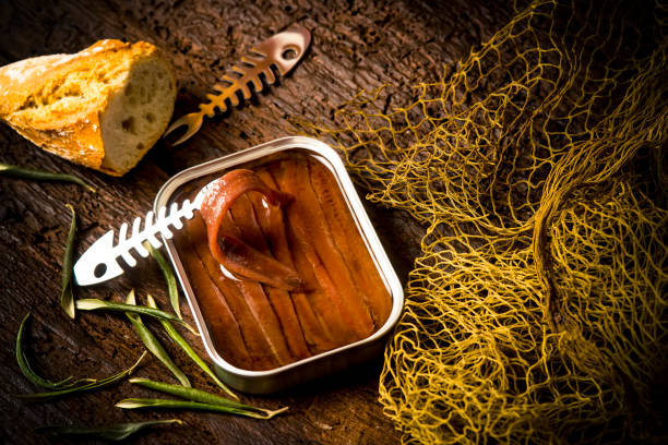 Salted anchovy fillets in olive oil tin can Salted anchovy fillets in olive oil tin can.Artisan anchovies from Cantabrian sea salting with olive oil on a rustic wooden table anchovy stock pictures, royalty-free photos & images
