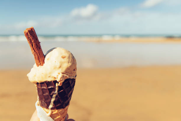 pov salted caramel ice cream cone at fistral beach, newquay, cornwall on a sunny september day. - ice cream cone stock pictures, royalty-free photos & images