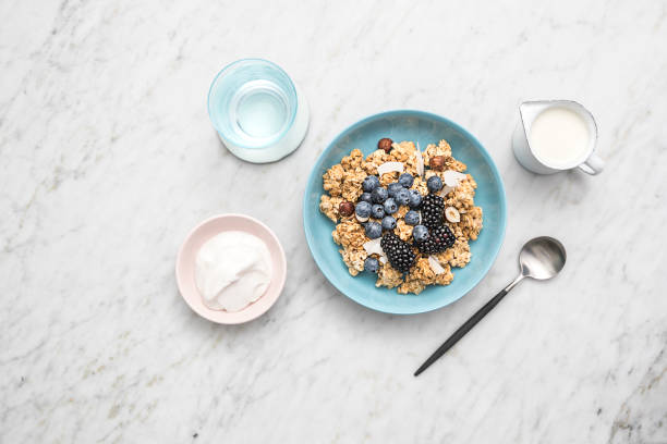salted caramel muesli/granola cereal bowl with fruit and yoghurt - anthony mcgovern stock photos and pictures