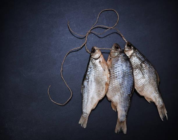 Gesalzener getrockneter Fisch auf dunklem Hintergrund. Salziger Trockenflussfisch. Essen. Top-Ansicht mit Kopierraum – Foto