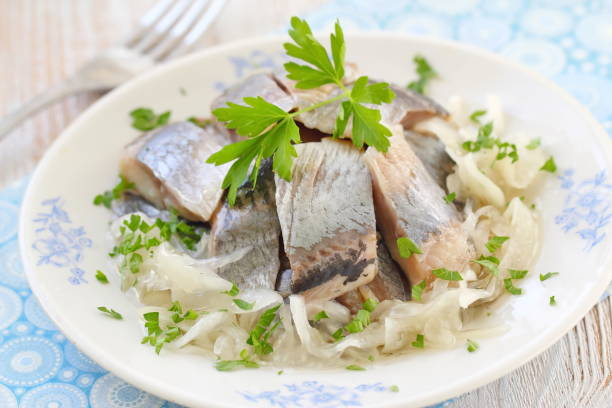 salted herring fillet with oil, marinated onion and fresh parsley - herring stock photos and pictures