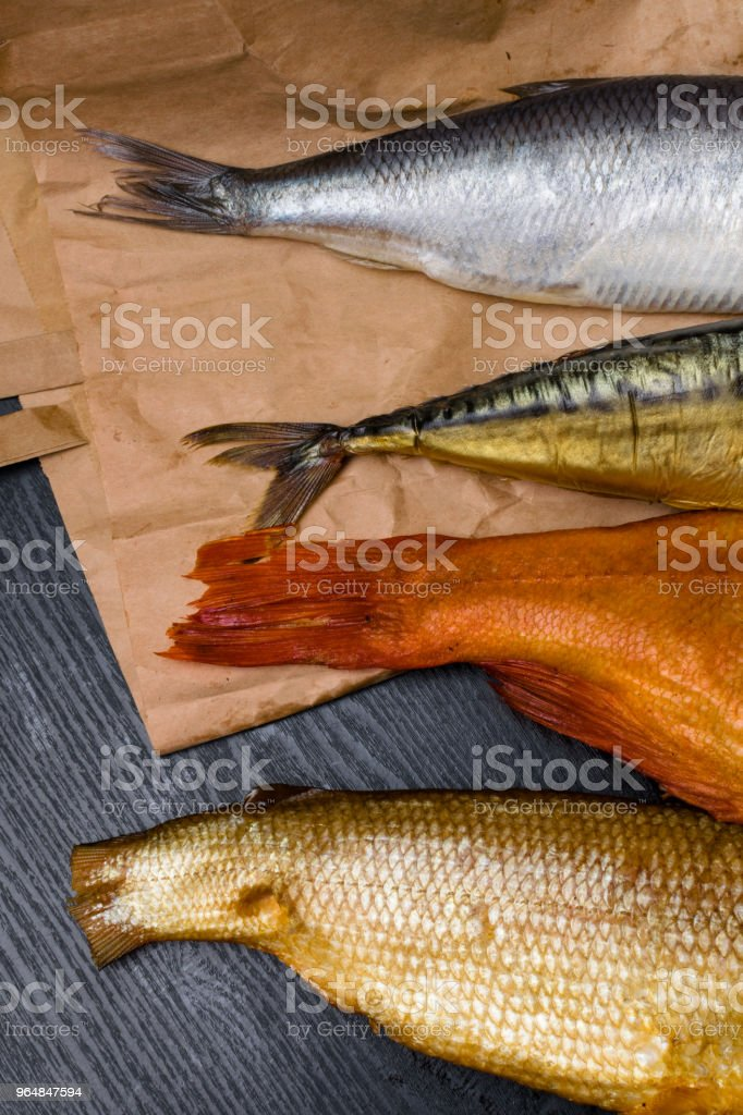 salted herring, smoked mackerel, perch and sig from Baikal on the paper bag in the black wooden background royalty-free stock photo