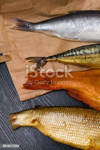 raw salted herring, smoked mackerel, perch and sig from Baikal on the paper bag in the black wooden background. Fish tails
