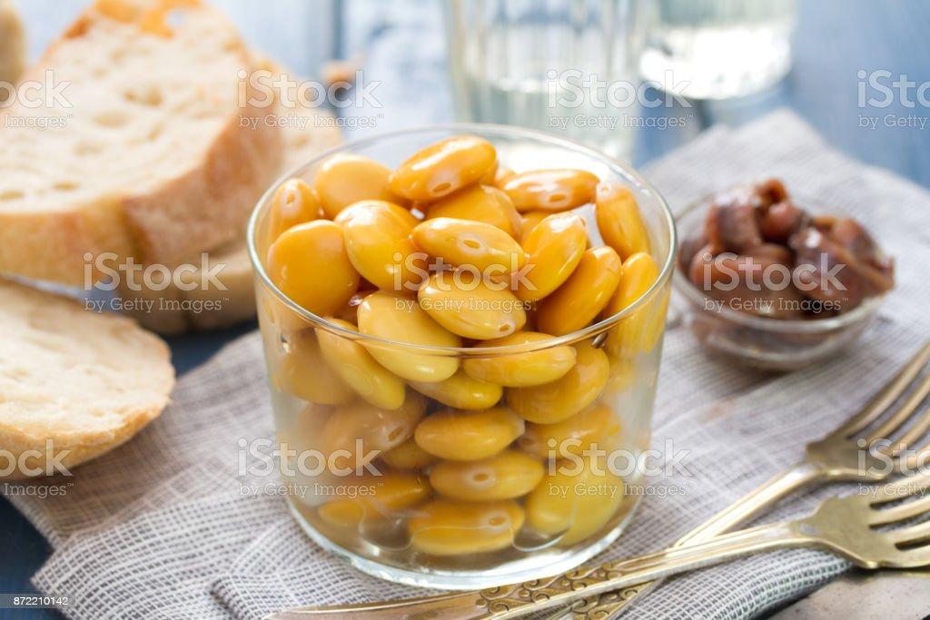 altramuces salados en cristal con Copa de vino - foto de stock