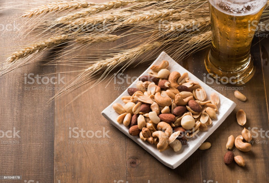 Salted mix cocktail nuts with beer and barley flower stock photo