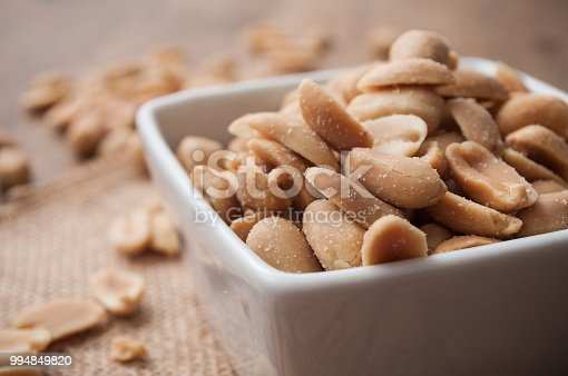 closeup of salted peanuts in a porcelain bowl on wooden background