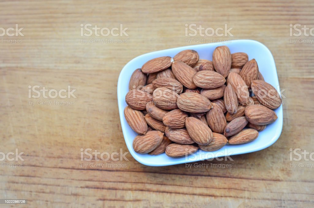 Salted roast organic almonds on a white plate on wood background