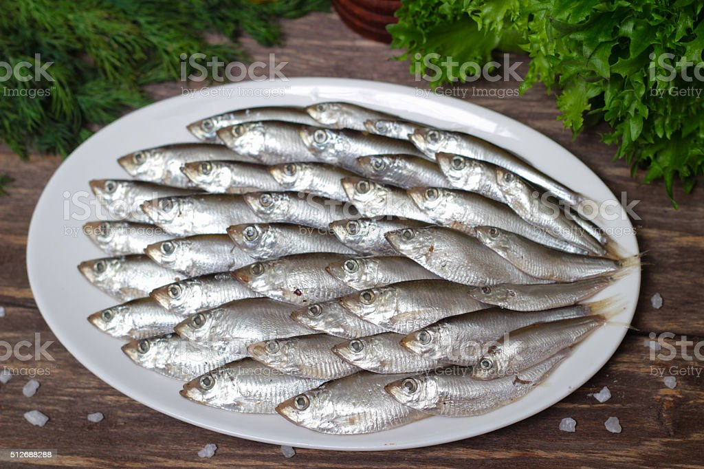 Salted sprat fish with greens on a plate stock photo