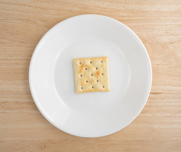 Saltine cracker on a plate atop wood table - foto de acervo