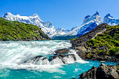 Beautiful Patagonia landscape photo at Salto Grande Waterfall with the Andes mountain range in the background at Torres del Paine National Park, Chile.