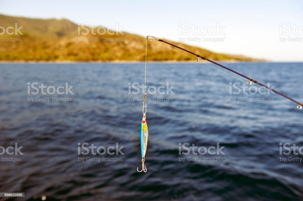 Saltwater fishing - rod with wobbler and blue sea water stock photo