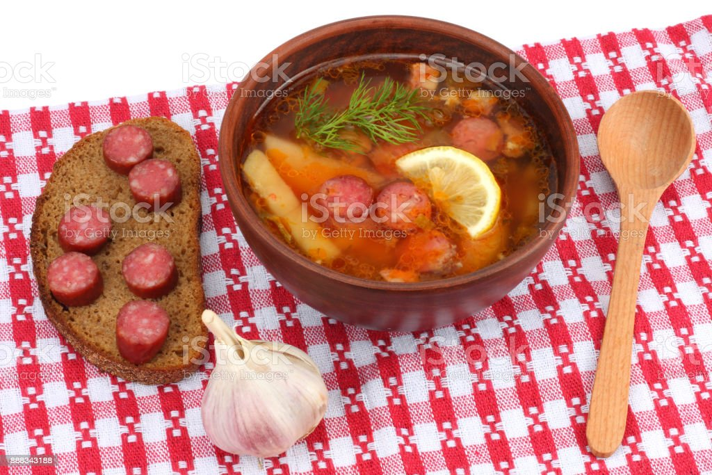 saltwort russian beef, pork and sausage soup solyanka with lemon, salami in plate on red cloth stock photo