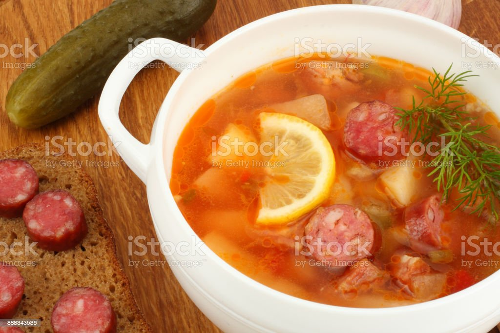 saltwort russian beef, pork and sausage soup solyanka with lemon, salami in plate on wooden background stock photo