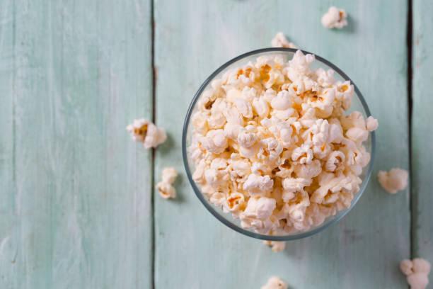 salziges Popcorn auf türkisfarbener Holzoberfläche – Foto