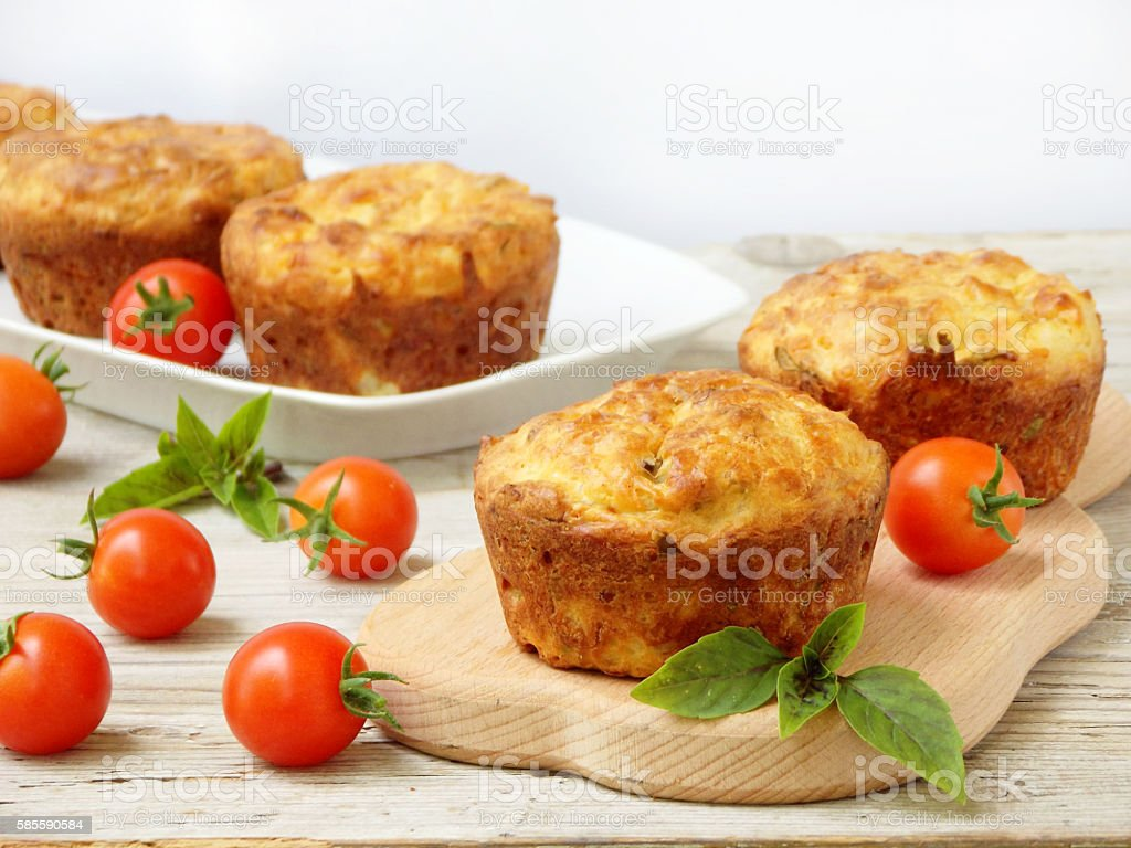 salty snack cakes muffins with cheese, tomatoes and basil stock photo