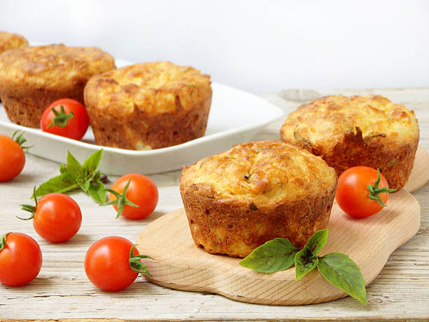 salty snack cakes muffins with cheese, tomatoes and basil - savory food stock photos and pictures