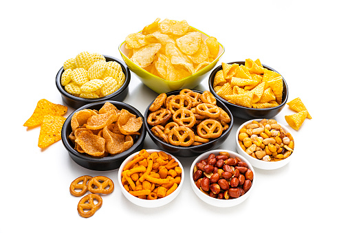 Party food: assortment of salty snacks in bowls shot on white background. High angle view. Predominant colors are yellow and white. High resolution 42Mp studio digital capture taken with SONY A7rII and Zeiss Batis 40mm F2.0 CF lens