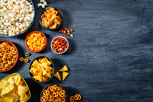 Party food: assortment of salty snacks in bowls shot from above on dark slate table. The composition includes potato chips, popcorn, corn bugles, pretzels, peanut, cheese sticks and others. The composition is at the left of an horizontal frame leaving useful copy space for text and/or logo at the right. Predominant colors are yellow and black. High resolution 42Mp studio digital capture taken with SONY A7rII and Zeiss Batis 40mm F2.0 CF lens