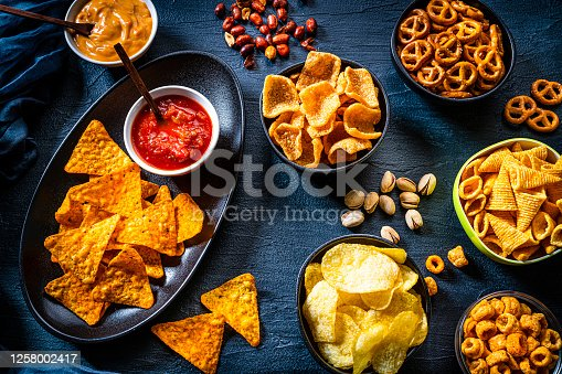 Party food: assortment of salty snacks shot from above on dark slate background. The composition includes nachos and salsa, corn bugles, pretzels, peanut, potato chips and others. Predominant colors are black, red and yellow. High resolution 42Mp studio digital capture taken with SONY A7rII and Zeiss Batis 40mm F2.0 CF lens